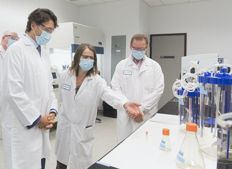 Justin Trudeau is surrounded by scientists, in a lab