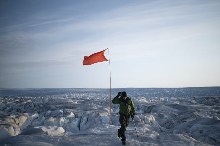 A person walks away from a red flag waving out on the ice.