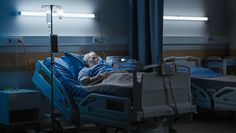 An elderly man with a breathing mask lays in a hospital bed in a dark ward room.