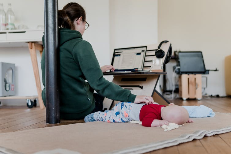 A woman sits on the ground with one hand on a sleeping baby and the other typing at a laptop