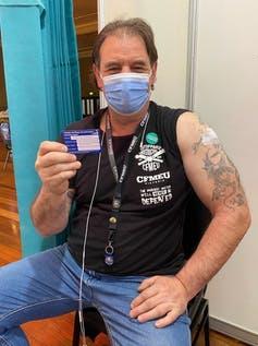The CFMEU's Victorian state secretary John Setka shows his vaccination card.