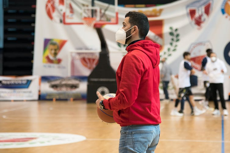A man inside a recreation facility wears a mask and holds a basketball, he's on a basketball court and people are playing in the background