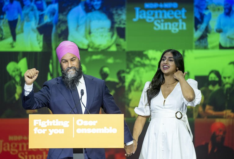 Singh pumps his fist while holding his wife's hand