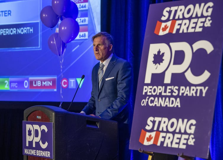 Bernier speaks from a podium with a party banner in the foreground