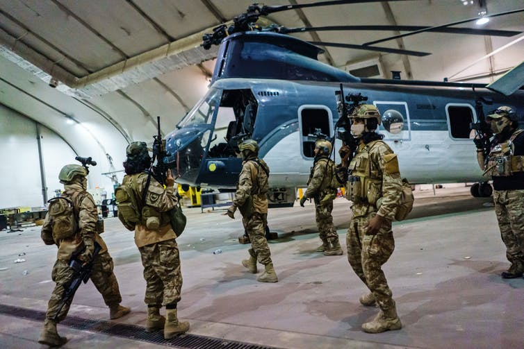 Soldiers stand near a helicopter