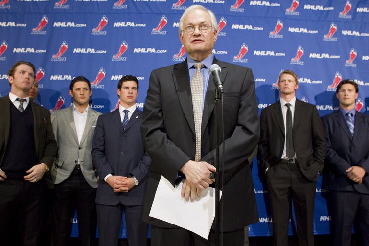 Man in a suit holding sheaf of papers stands in front of microphone. Five other men in suits stand in the background.