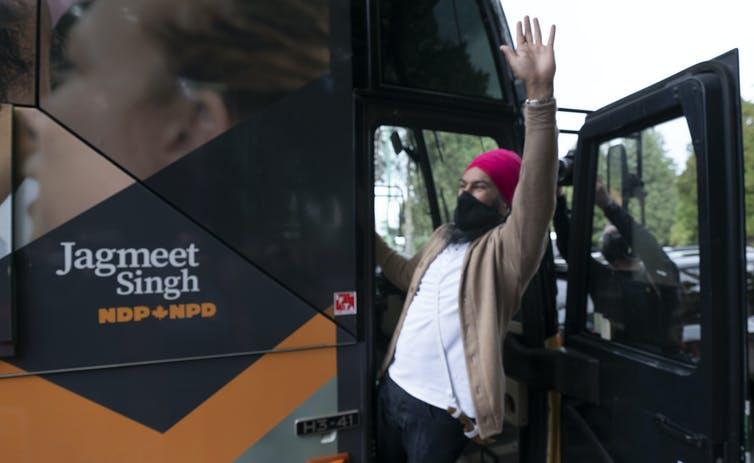 NDP Leader Jagmeet Singh waving in the doorway of his campaign bus.