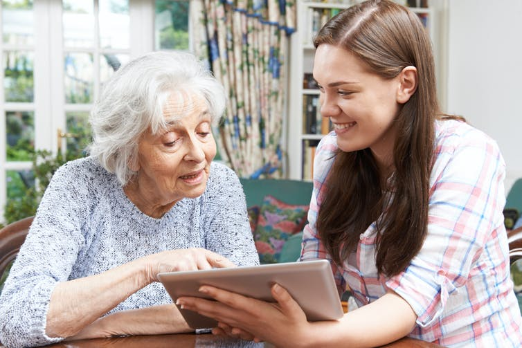 Grandmother looks at ipad with her granddaughter