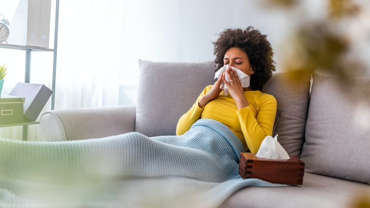 A woman with a viral infection blowing her nose