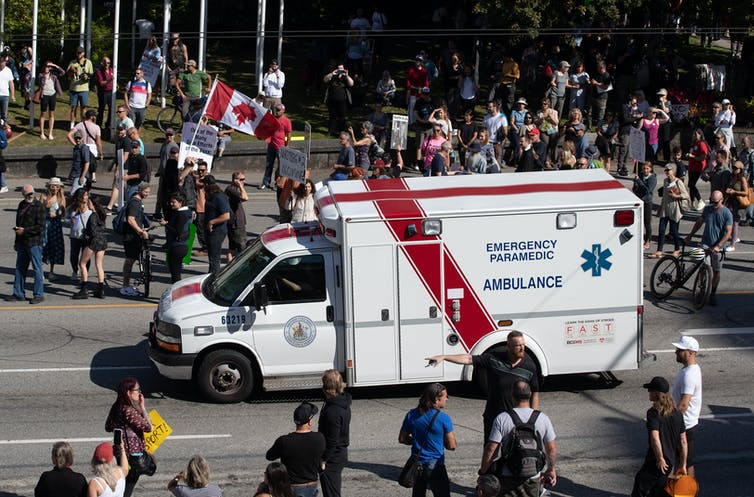 An ambulance passes through a crowd of people protesting COVID-19 vaccine passports and mandatory vaccinations