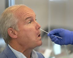 Conservative Leader Erin O'Tool in profile, being tested with a nasal swab