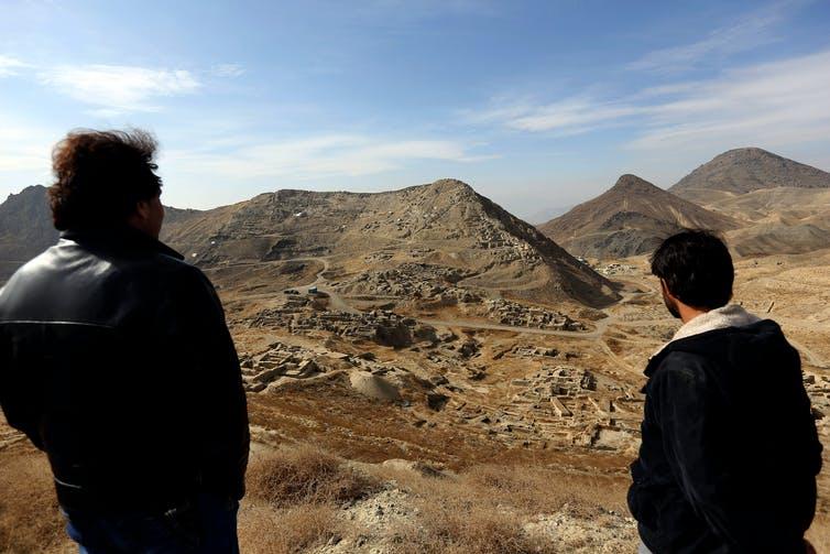 Two men look across the Men Aynak valley of Afghanistan