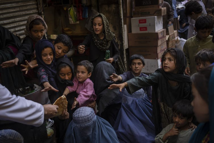 Women and children in Afghanistan seeking food donations.