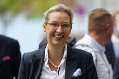 A woman smiling in a blazer, glasses and pearls.