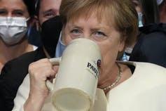 Angela Merkel sips on a beer.