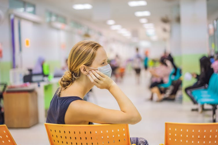 Woman in a mask waits in hospital waiting room.