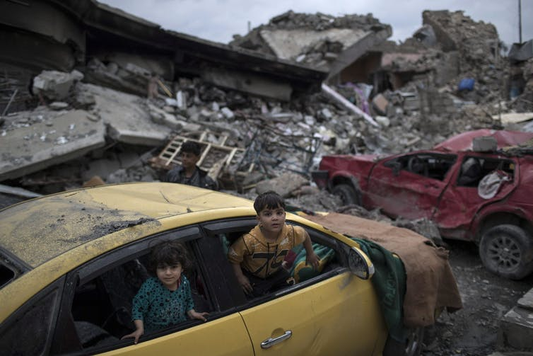 Children play in a damaged car amid piles of rubble.