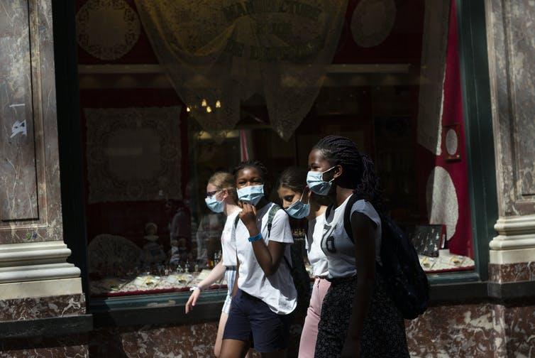 Girls walk wearing face masks on a street.