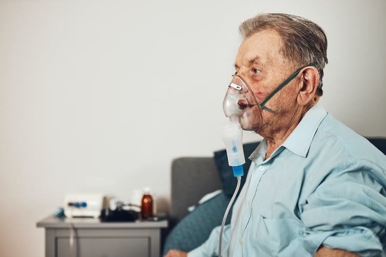 Older man sits on the edge of his bed, breathing through a nebuliser mask.