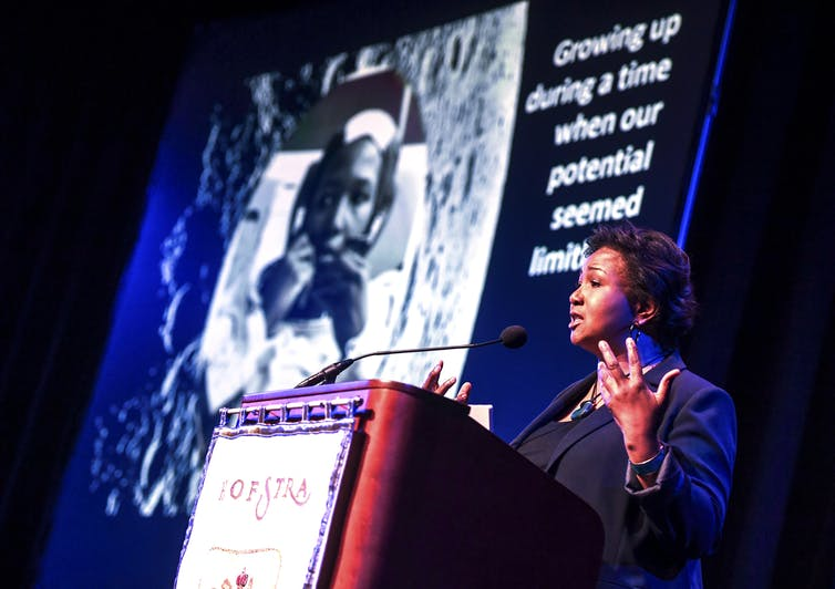 An African American woman speaks at a conference.