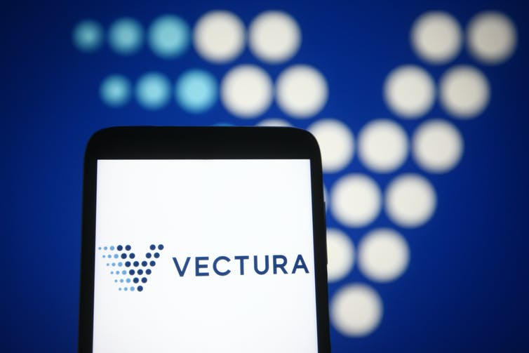 Blue-spotted 'V' Vectura logo on a smartphone and in the background.