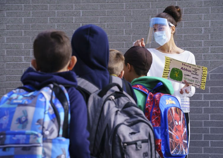 A teacher in face shield faces students in a yard.
