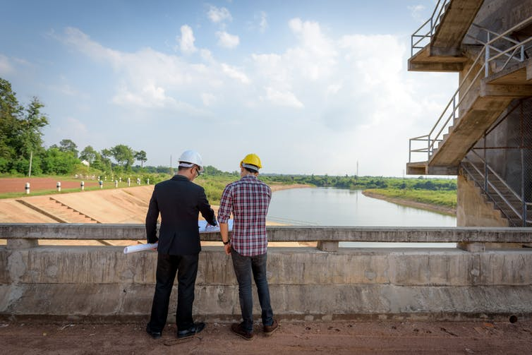 two male engineers look at dam