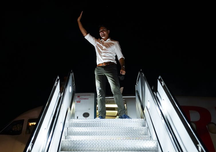 Trudeau waves from the stairs of his campaign plane.