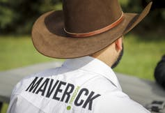A man wearing a cowboy hat and a shirt that reads Maverick on the back is photographed from behind
