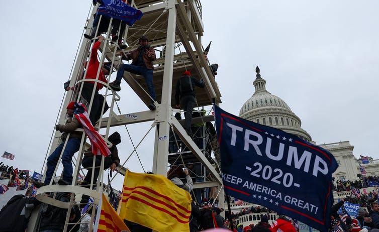 Rioters scale structures while flying flags outside the Capitol.