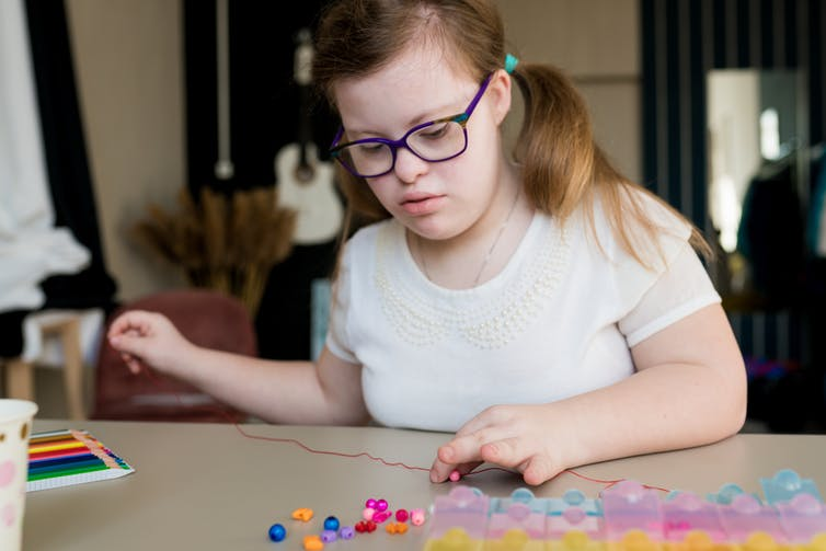 A disabled teen in glasses sits at a desk, beading a necklace.