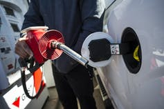 A person fills up a truck with gas.
