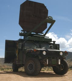 Dark green four-wheel truck with large octagonal antenna mounted on the roof