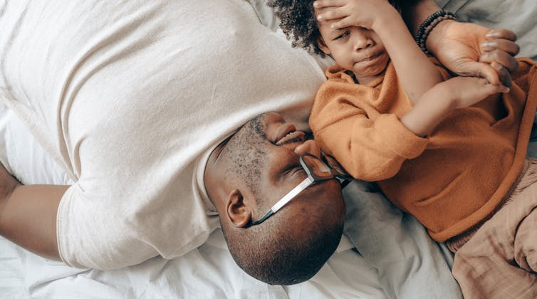 A father and child talk lying down and the boy looks a little apprehensive while the father holds his hand.