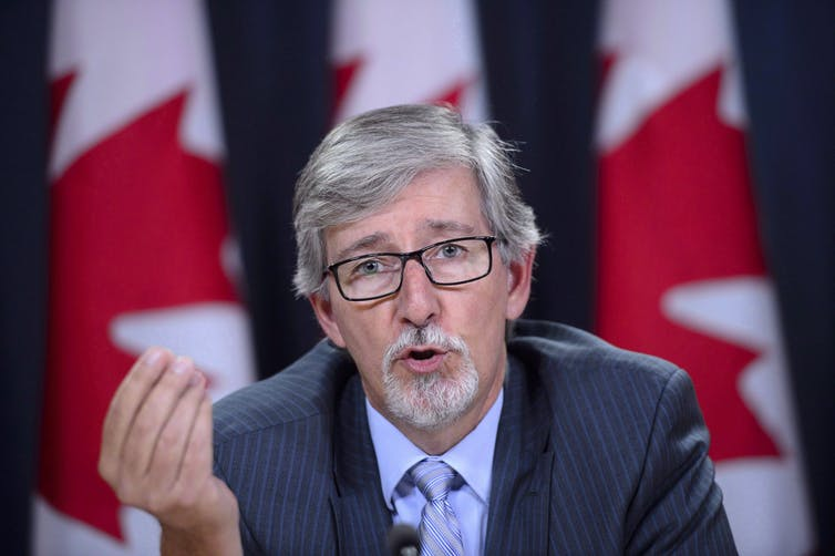 privacy commissioner Daniel Therrien sits at a news conference making a hand gesture with Canadian flags in the background