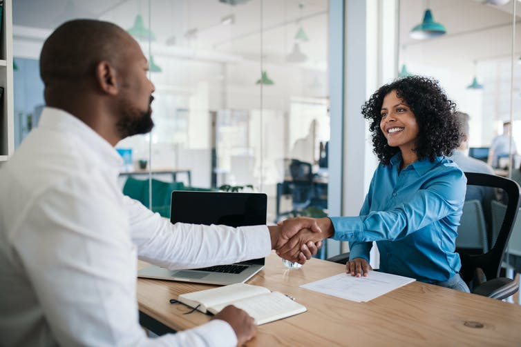 A man reaches his hand across a table to greet a woman, they're in an office setting, they're both smiling