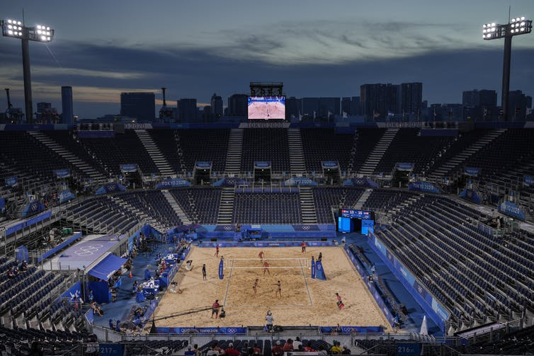 A beach volleyball game taking place in an empty stadium