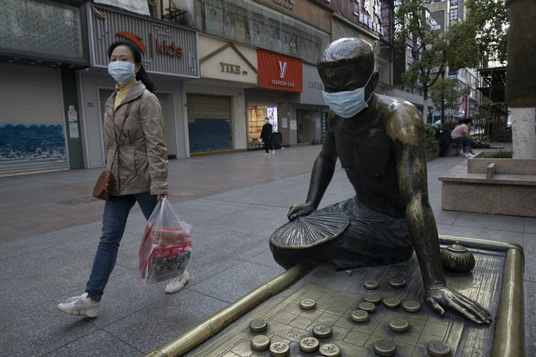 A woman wearing a surgical mask walks past a statue wearing a surgical mask.