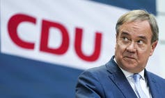 A man wearing glasses speaks with a CDU sign behind him.