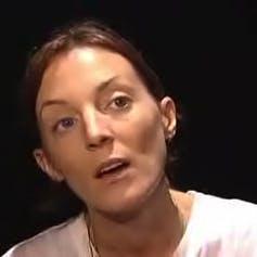 A woman with dark hair in a white shirt.