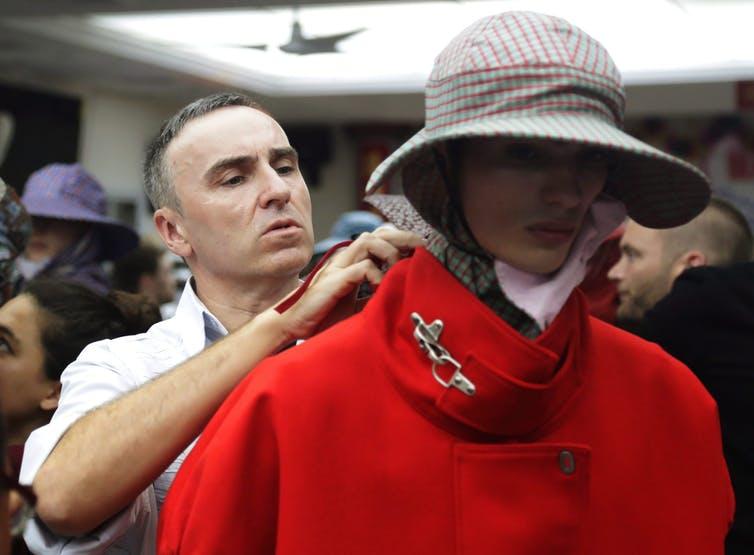 Raf Simons adjusts a model's coat.