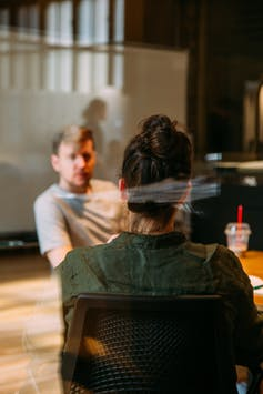 A man and woman talk in an office setting, the woman with her back to the camera.