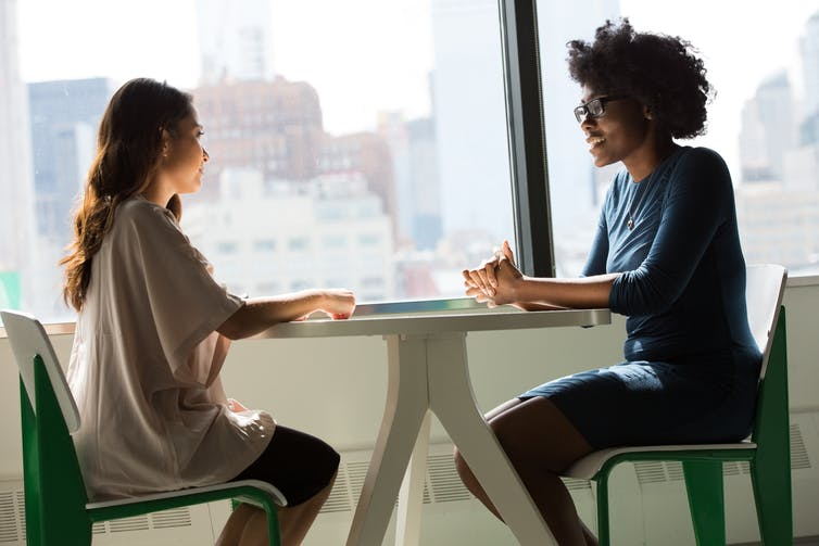 Two women sit talking at a table in an office setting.