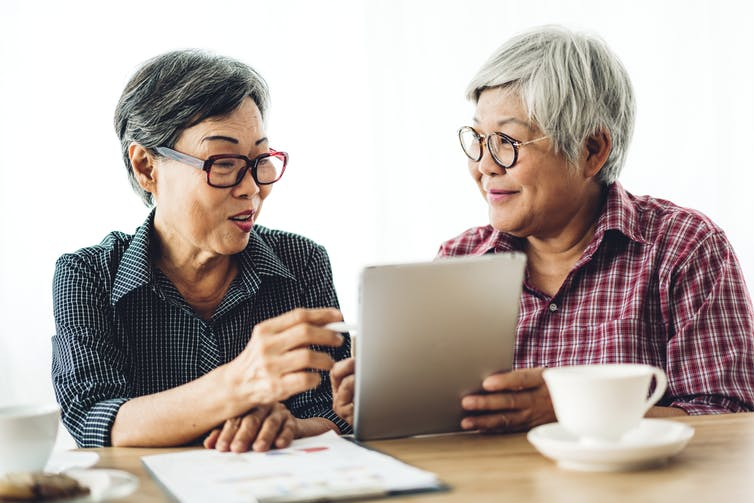 Two older women look at an iPad together