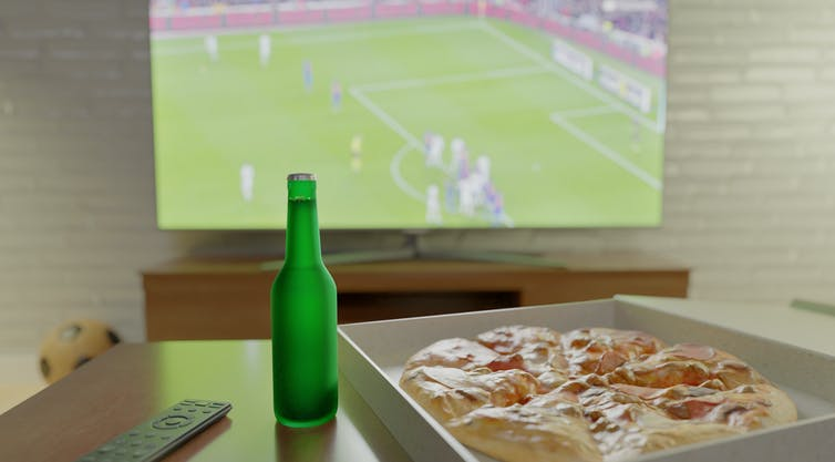 Bottle of beer and pizza on table in front of TV showing football game.