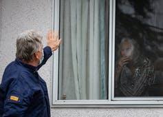 A man waves to an elderly woman through a window