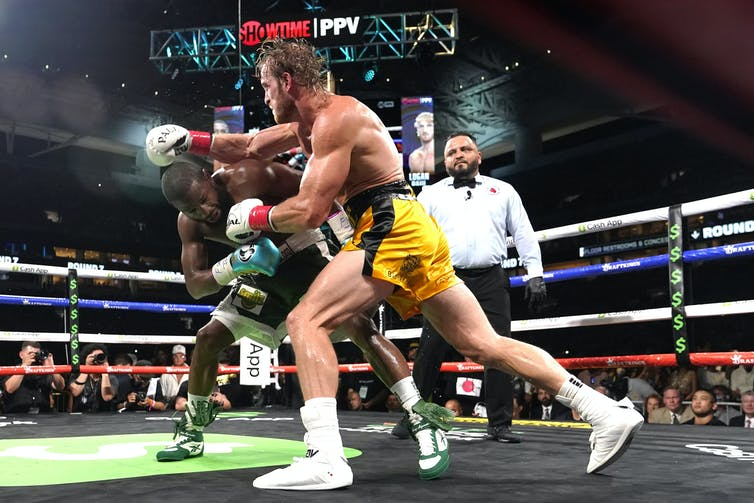 Two men box in a boxing ring with a referee in the background, the man in the foreground throws a right hook towards his ducking opponent