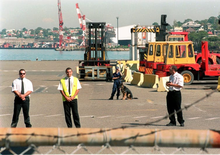 Private security guards and dogs keep watch at Patrick Corporation's dock at Sydney's Darling Harbour on April 8 1998, the day after the company fired all its 1,400 dock workers.