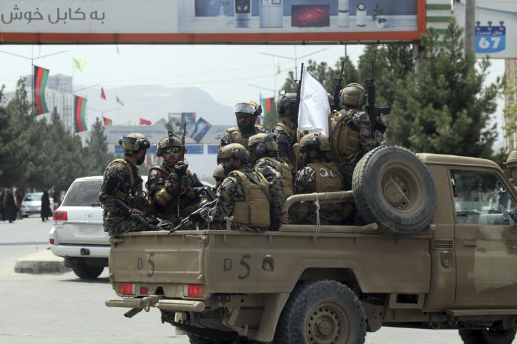 A truck of soldiers drives down a street