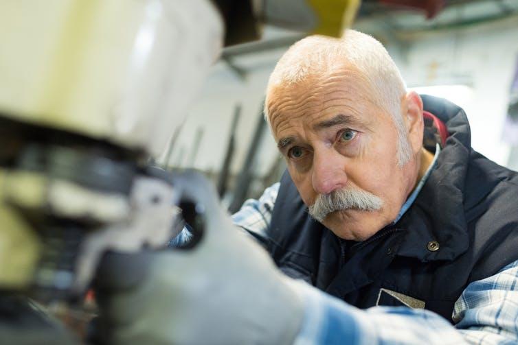 Older man working heavy machinery